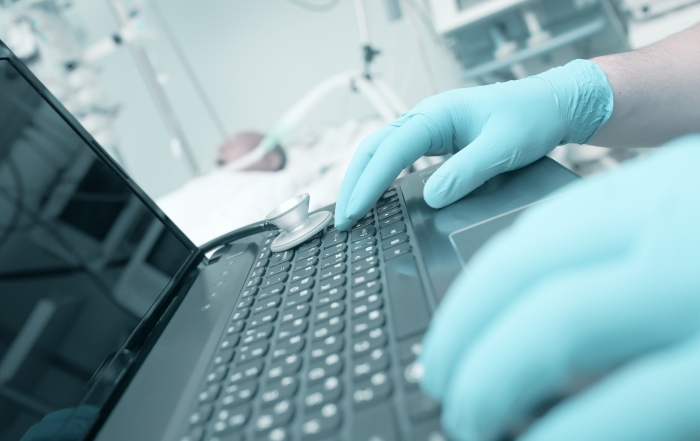 Doctor typing on laptop in the intensive care